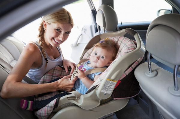Mother-buckling-baby-into-car-seat